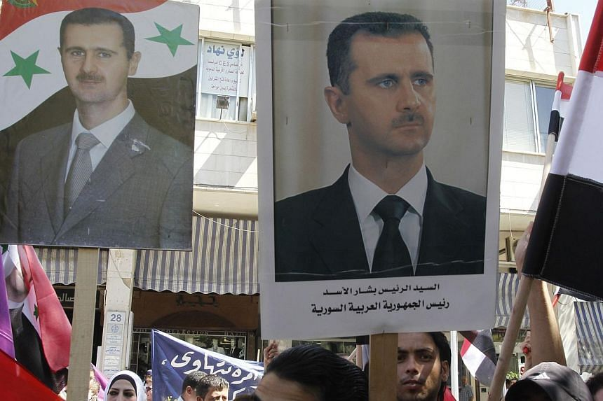 """Supporters of Syria's President Bashar al-Assad wave his posters during a rally in front of the parliament building under the slogan """"No aggression on Syria"""", in Damascus September 17, 2013.Bashar al-Assad insisted on Wednesday that Syria is no"""