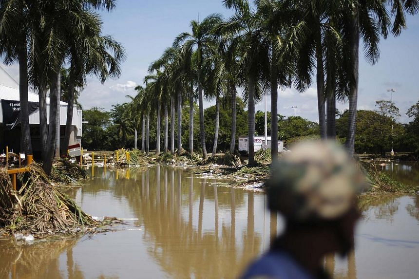 A soldier stands in a flooded neighbourhood in Acapulco September 18, 2013. The death toll from storms that have swept across Mexico rose to 80 on Wednesday, a civil protection official said. -- PHOTO: REUTERS