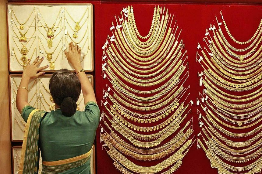 A saleswoman arranges a gold necklace inside a jewellery showroom in the southern Indian city of Kochi on April 16, 2013.India has called a meeting of top officials from the finance and trade ministries in New Delhi on Friday, Sept 20, 2013, to