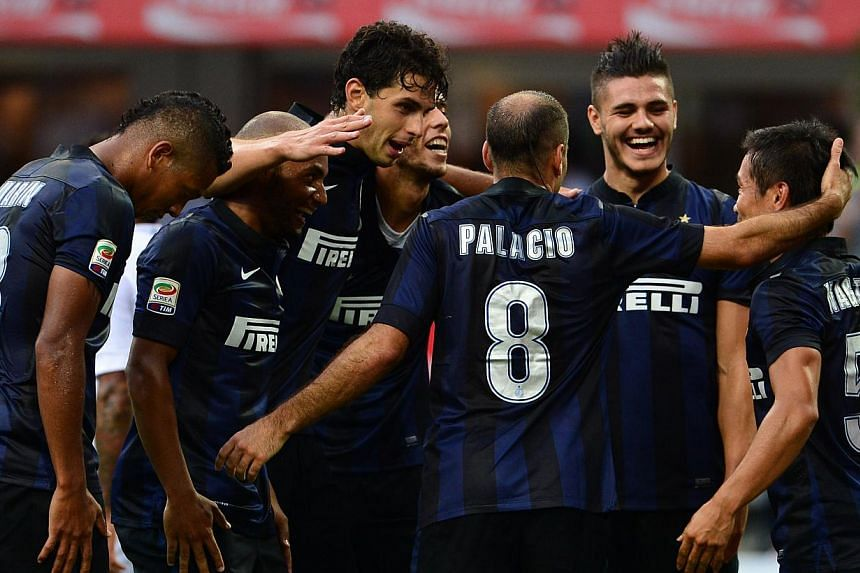 Inter Milan's Japanese midfielder Yuto Nagatomo (right) celebrates with teammates after scoring a goal during their Serie A football match against Genoa at San Siro Stadium in Milan on Aug 25, 2013. Inter Milan are edging closer to a deal with E