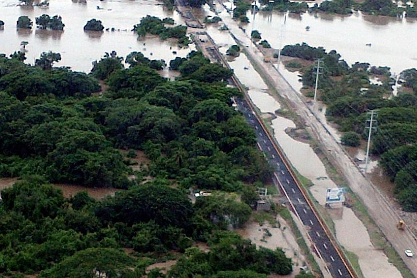 This handout photo taken and released on Wednesday, Sept 18, 2013, by Mexico's Interior Ministry press office shows an aerial view of flooding along a highway going to Acapulco, in the Mexican state of Guerrero, as heavy rains hit the country. -- PHO