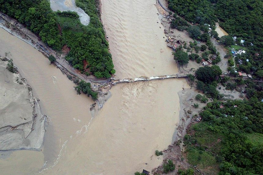 This handout photo taken and released on Wednesday, Sept 18, 2013, by Mexico's Interior Ministry press office shows an aerial view of a damaged bridge along a highway going to Acapulco, in the Mexican state of Guerrero, as heavy rains hit the co