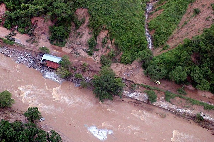 This handout photo taken and released on Wednesday, Sept 18, 2013, by Mexico's Interior Ministry press office shows an aerial view of landslides along a highway going to Acapulco, in the Mexican state of Guerrero, as heavy rains hit the country. -- P