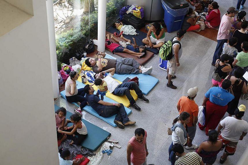 Tourists camp out at a convention centre before being airlifted out of Acapulco on Sept 18, 2013. Thousands of frustrated tourists lined up under sweltering heat on Wednesday to board airlifts out of the flooded resort of Acapulco while a drenched Me