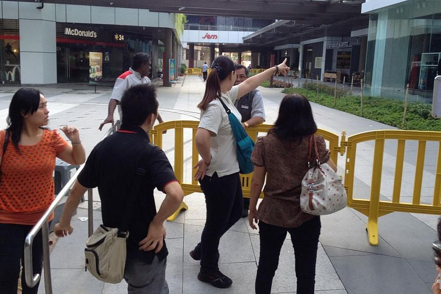 Retail staff outside JEM mall on Thursday morning, Sept 19, 2013. -- ST PHOTO: KUA CHEE SIONG