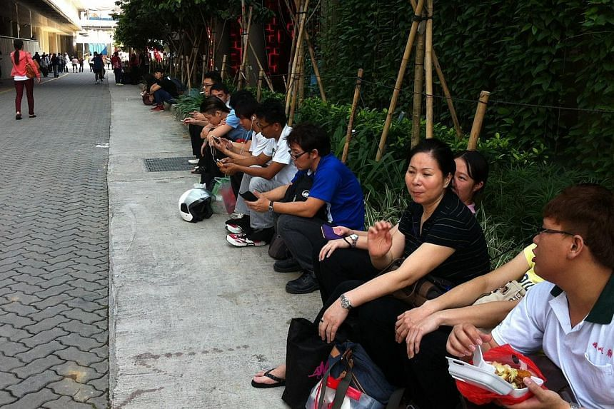 Employees of tenants like Sushi Tei sitting around. They arrived this morning and realized that the mall was closed. They are waiting for their manager to tell them what to do.-- ST PHOTO: JESSICA LIM