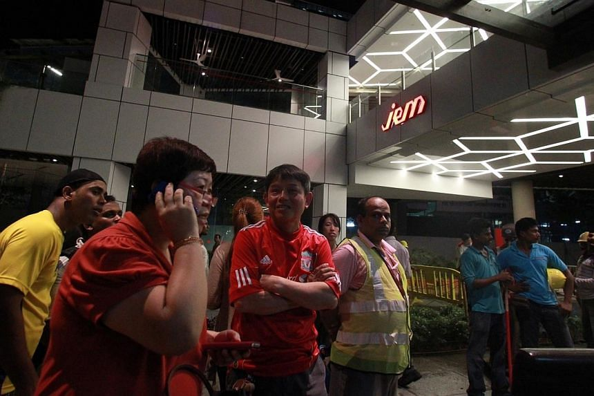 The crowd outside Jem mall at around 11.50pm on Wednesday, Sept 18, 2013. Tenants at the mall, where a ceiling collapsed on Wednesday, were still locked out of the building two hours after the incident. -- ST PHOTO: NEO XIAOBIN