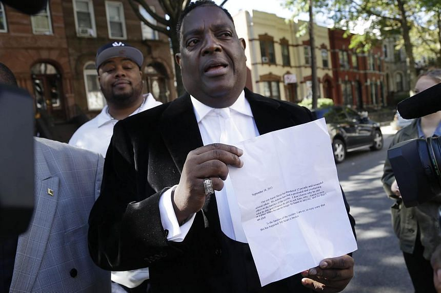 Bishop Gerald Seabrooks shows a statement made by Cathleen Alexis, mother of Washington Navy Yard gunman Aaron Alexis, in New York's Brooklyn borough on Wednesday, Sept 18, 2013. The mother of the defence contractor who gunned down 12 people at the W