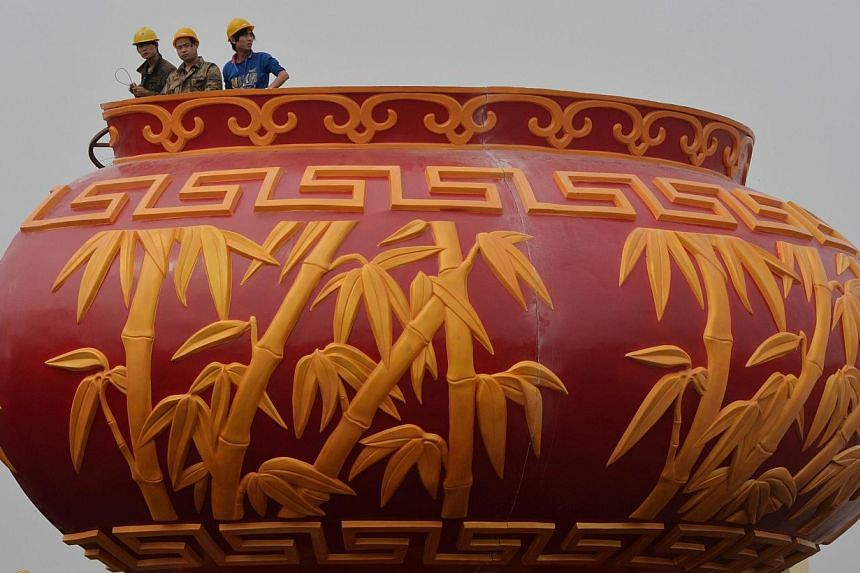 Workers install a giant vase as part of the upcoming Chinese National Day celebrations at Tiananmen Square in Beijing on Sept 19, 2013. The seven-day holiday sees millions of members of China's newly wealthy and mobile middle-class travel locally and