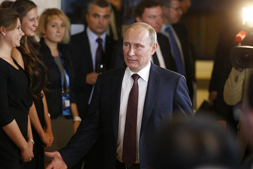 Russian President Vladimir Putin gestures as he leaves the final plenary meeting of the Valdai International Discussion Club in the Novgorod Region, on the banks of Lake Valdai, Russia, on Sept 19, 2013. Mr Putin said on Thursday he could not be 100