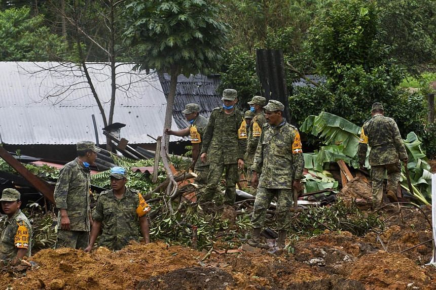 Mexican soldiers work on the site of a landslide in La Pintada, state of Guerrero, Mexico, on Sept 19, 2013, as heavy rains hit the country. Around 100 soldiers and police officers arrived in the village on Thursday, some by helicopter, others after