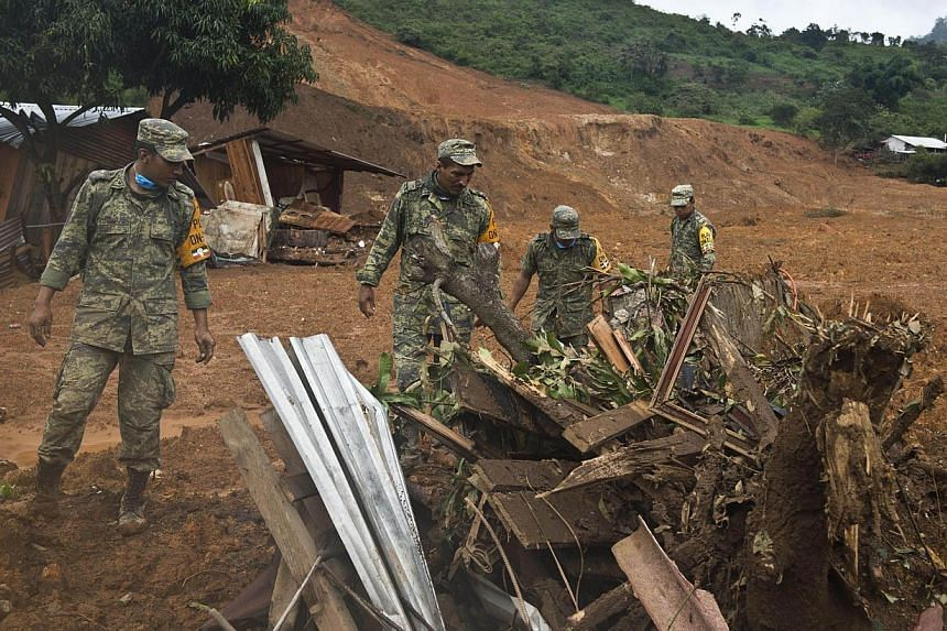 Mexican soldiers look for bodies on the site of a landslide in La Pintada, state of Guerrero, Mexico, on Sept 19, 2013, as heavy rains hit the country. Around 100 soldiers and police officers arrived in the village on Thursday, some by helicopter, ot