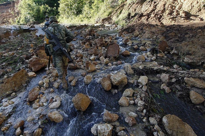 Mexican soldiers walk along a damaged road to bring relief aid to La Pintada, state of Guerrero, Mexico, on Sept 19, 2013, as heavy rains hit the country. Around 100 soldiers and police officers arrived in the village on Thursday, some by helicopter,