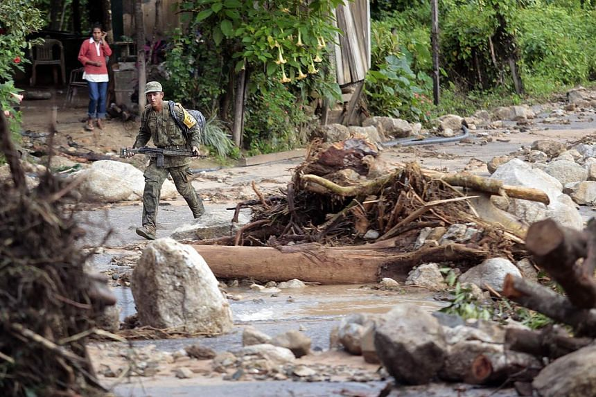 A Mexican soldier walks along a damaged road toward La Pintada, state of Guerrero, Mexico, on Sept 19, 2013, as heavy rains hit the country. Around 100 soldiers and police officers arrived in the village on Thursday, some by helicopter, others after