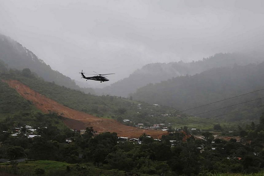 A helicopter of the federal police flies over a mudslide in the village of La Pintada, in the Mexican state of Guerrero on Sept 19, 2013.Mexican authorities lost contact on Thursday with a federal police Black Hawk helicopter that was conductin