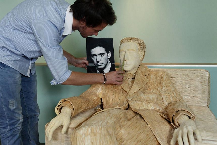 Tomislav Horvat, 24, inspects his sculpture of Hollywood actor Al Pacino that is made of 117,000 matches in Podturen, north Croatia, Thursday, Sept 19, 2013. -- PHOTO: REUTERS