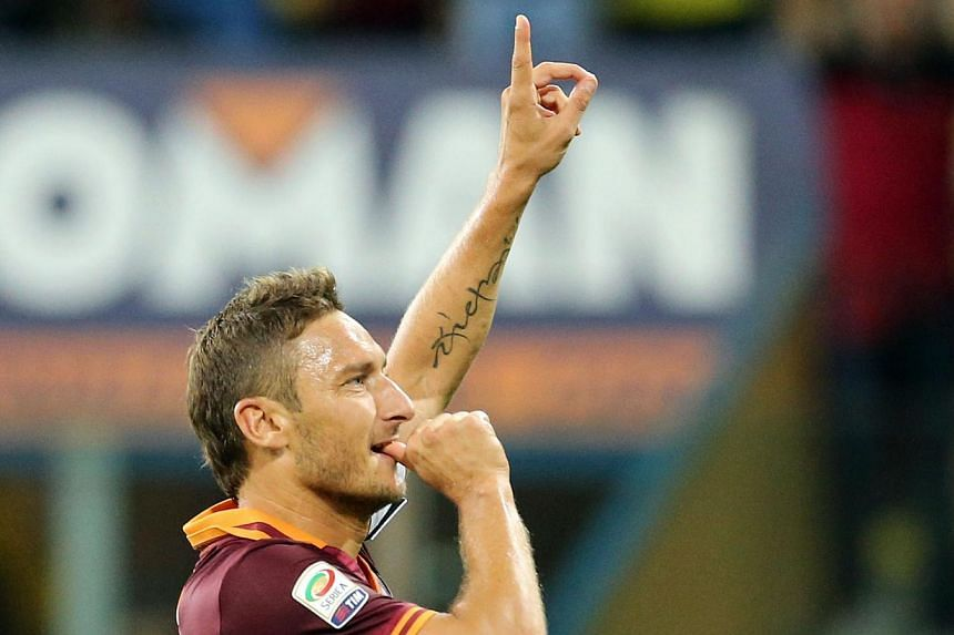 AS Roma's captain Francesco Totti celebrates after scoring against Parma at the Tardini stadium on Sept 16, 2013.Totti signed a new contract on Friday, Sept 19, 2013, that will keep him at Roma until just before his 40th birthday. -- PHOTO: AFP