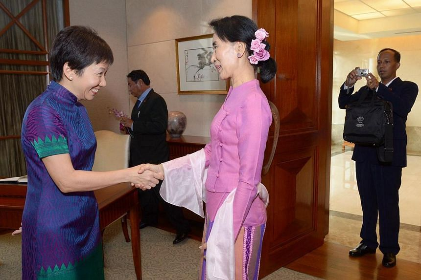 Myanmar's opposition leader Aung San Suu Kyi (centre) began her first visit to Singaporeon Friday,Sept 20, 2013,by calling on Second Minister for Foreign Affairs Grace Fu (left). -- ST PHOTO:DESMOND WEE