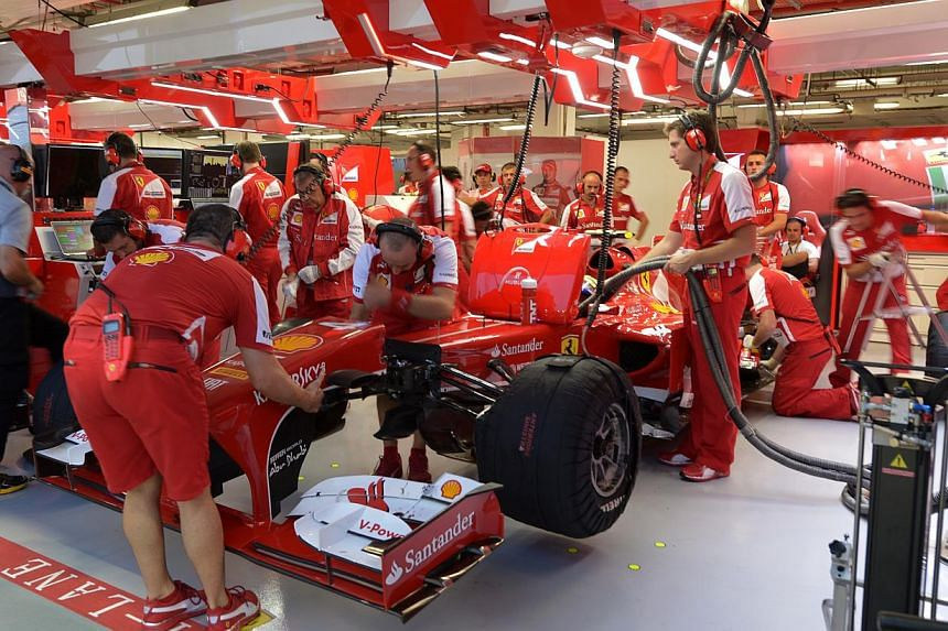 The Ferrari crew working on Felipe Massa's car in the garage during the first practice session of the Formula One Singapore Grand Prix 2013 on Friday, Sept 20, 2013. -- ST PHOTO: CAROLINE CHIA