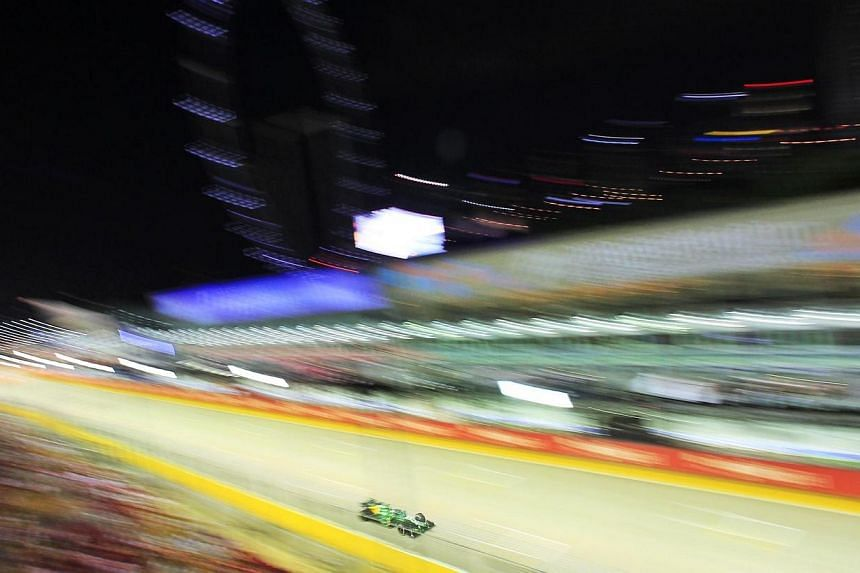 Holland's Giedo van der Garde of Caterham F1 Team steers past the F1 pit building during the first practice session of the Formula One SingTel Singapore Grand Prix at the Marina Bay street circuit on Friday, Sept 20, 2013. -- ST PHOTO: KEVI