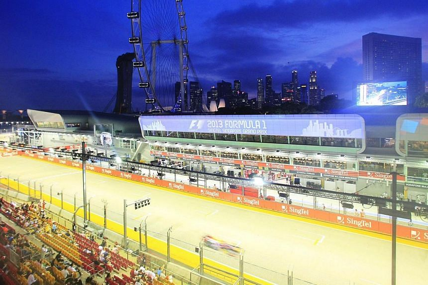 Germany's Sebastian Vettel of Red Bull Racing steers past the F1 pit building during the first practice session of the Formula One SingTel Singapore Grand Prix at the Marina Bay street circuit on Friday, Sept 20, 2013. -- ST