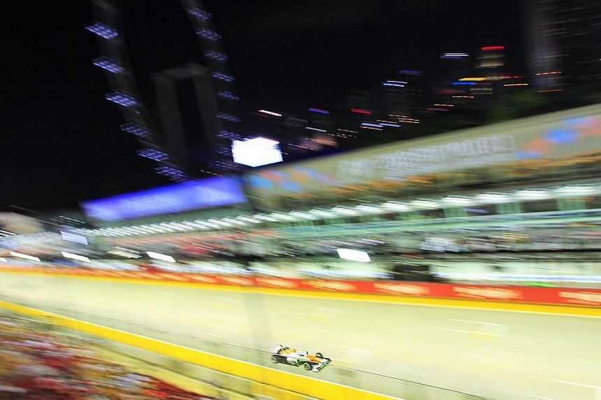 Germany's Adrian Sutil of Sahara Force India steers past the F1 pit building during the first practice session of the Formula One SingTel Singapore Grand Prix at the Marina Bay street circuit on Friday, Sept 20, 2013. -- ST P