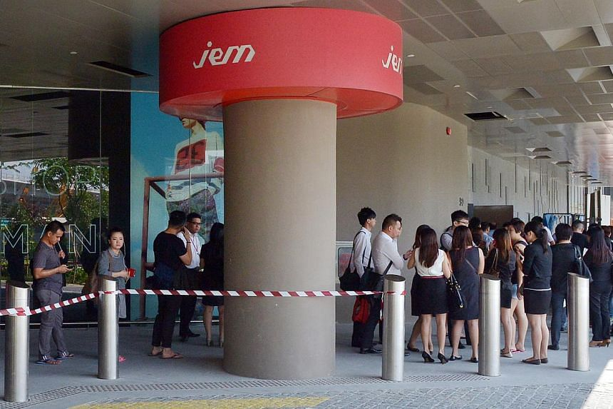 Staff of Jem mall's tenants queueing up to register their names before they were allowed to enter the building to retrieve their valuables yesterday. -- ST PHOTO: KUA CHEE SIONG