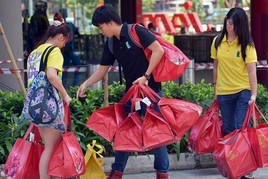 Mr Chung Kuan (above, centre), who works at Peony Jade Restaurant's booth in Jem's basement, and two other employees carrying out boxes of mooncakes to be sold at its Takashimaya outlet instead. -- ST PHOTO: KUA CHEE SIONG