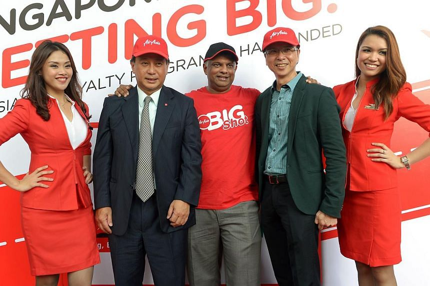 AirAsia's group chief executive Tony Fernandes flanked by DBS' Singapore country head Sim S. Lim (with grey tie) and StarHub CEO Tan Tong Hai at yesterday's launch of the new loyalty programme.