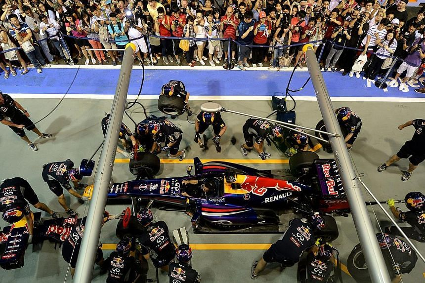 Members of the public thronging the garage of F1 world champions Red Bull during the Pit Lane experience last night. -- ST PHOTO: MUGILAN RAJASEGERAN