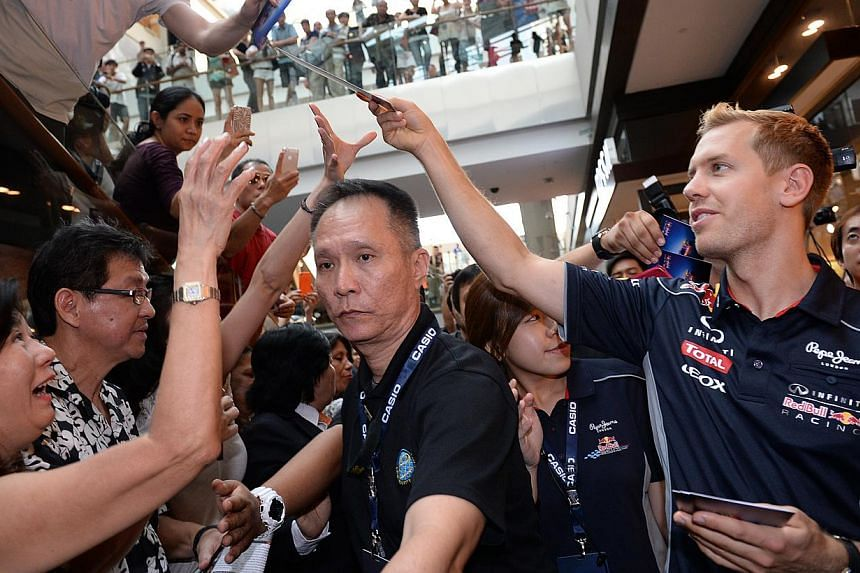 F1 world champion Sebastian Vettel handing out autographed cards of himself to fans during the grand opening of a new Casio watch store at Marina Bay Sands yesterday.