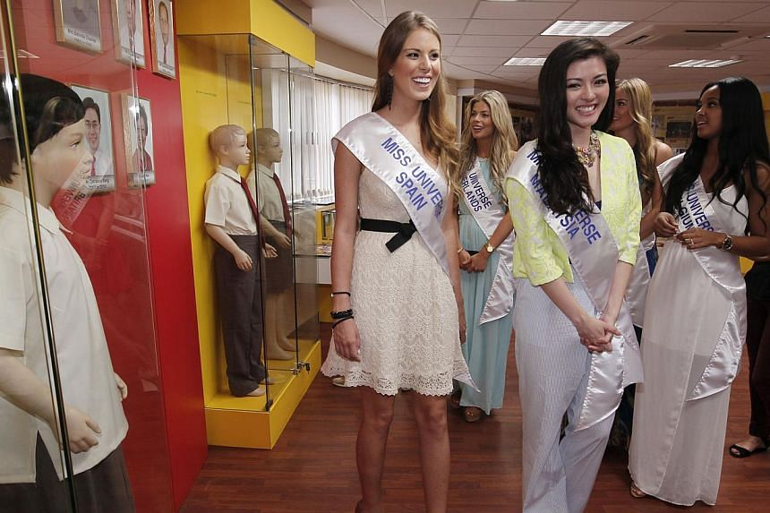 Miss Universe Spain 2013 Andrea Huisgen (left), Miss Universe Malaysia 2013 Carey Ng (centre) and the six other Miss Universe 2013 contestants take a tour of Bukit Batok Secondary School during a visit on Friday, Sept 20, 2013. -- ST PHOTO: MARK