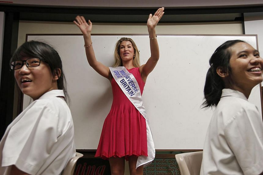 Miss Universe Great Britain 2013 Amy Willerton (centre) waves to Bukit Batok Secondary School students as she introduces herself during a visit to the school with other Miss Universe 2013 contestants, on Friday, Sept 20, 2013. -- ST PHOTO: MARK