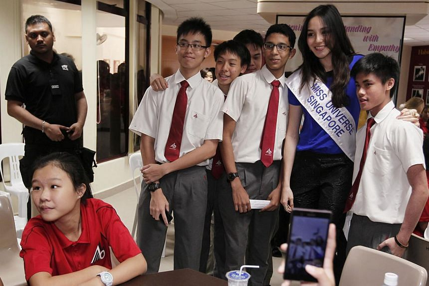 Miss Singapore Universe 2013 Shi Lim poses for photos with 15-year-old Bukit Batok Secondary School students (from left) Bryan Ng, Ong Yu Xian, Aara Noronha, and Zachary Tan during a visit to the school with other Miss Universe 2013 contestants, on F