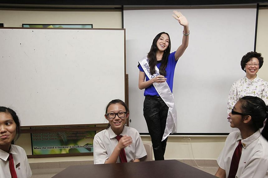 Miss Universe Singapore 2013 Shi Lim (centre) waves to Bukit Batok Secondary School students as she introduces herself during a visit to the school with other Miss Universe 2013 contestants, on Friday, Sept 20, 2013. -- ST PHOTO: MARK CHEONG