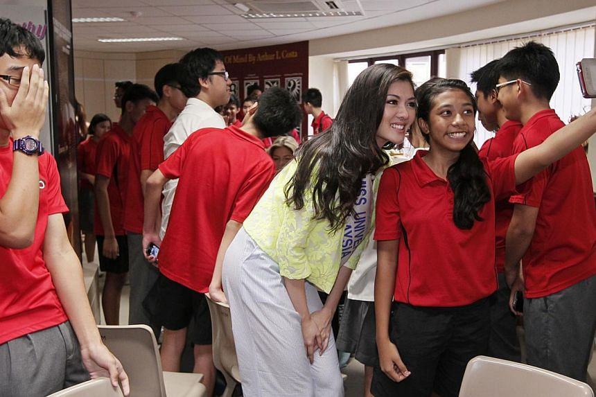 Miss Universe Malaysia 2013 Carey Ng (centre) poses for a photo with Friends-of-Singa ambassador and Bukit Batok Secondary School student Saranya Ramesh, 14, during a visit to the school with other Miss Universe 2013 contestants, on Friday, Sept 20,