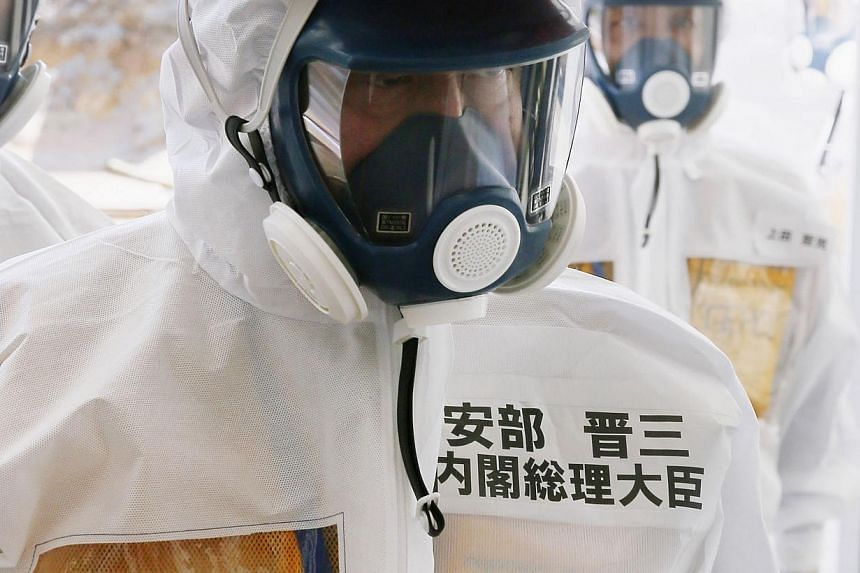 Japan prime minister Shinzo Abe arrives in a protective suit at Tepco's Fukushima Daiichi nuclear power plant in Okuma, Fukushima Prefecture, on Sept 19, 2013. Tepco wrote the second Chinese character of his name (on the suit) wrongly. -- PHOTO: AFP