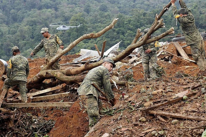 Mexican soldiers work on the site of a landslide in La Pintada, state of Guerrero, Mexico, on Sept 19, 2013, as heavy rains hit the country.Around 100 soldiers and police officers arrived in the village on Thursday, some by helicopter, others a