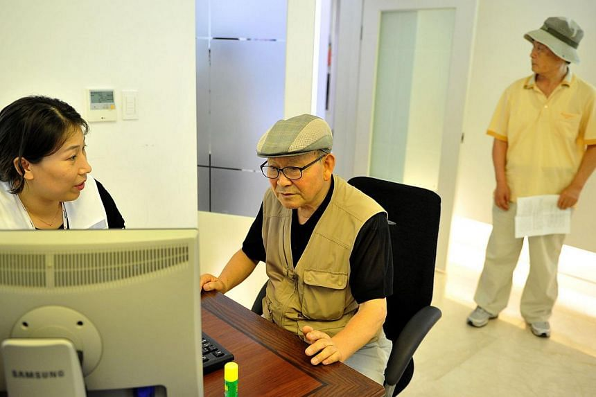 Lee Han Soo (centre), 78, checks his application with an official from the Red Cross in Seoul to see if it was possible to take part in upcoming reunions with relatives in North Korea, while Choi Jang Dong (right), 75, waits his turn, at the administ
