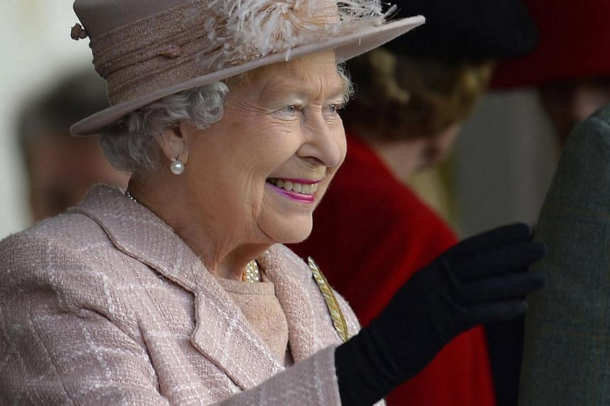 Britain's Queen Elizabeth II waves to the crowds as she arrives at the annual Braemar Highland Gathering in Braemar, Scotland, on Sept 7, 2013. A book on British royal pets says Queen Elizabeth II is so fond of her corgis that she personally supervis
