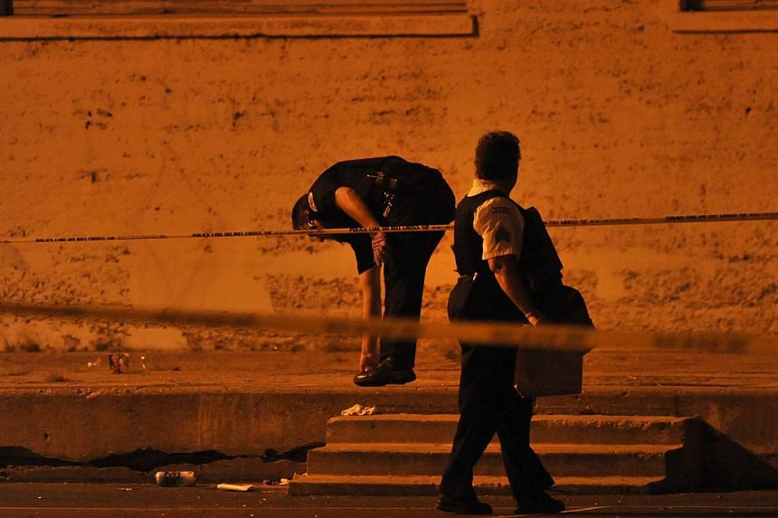 Chicago Police detectives investigate the scene where 13 people, including a three-year-old child, were shot in a city park on the south side of Chicago on Sept 19, 2013. Authorities said no one has been taken into custody in connection with the shoo