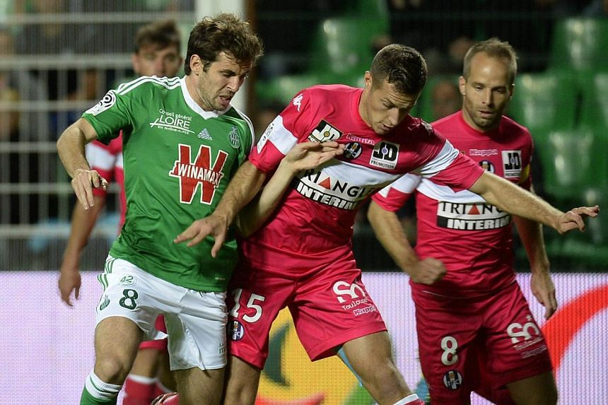 Saint-Etienne's French midfielder Benjamin Corgnet (left) vies with Toulouse's Serbian defender Uros Spajic (right) during the French L1 football match Saint-Etienne vs Toulouse on Sept 20, 2013 at the Geoffroy Guichard stadium in Saint-Etienne, east