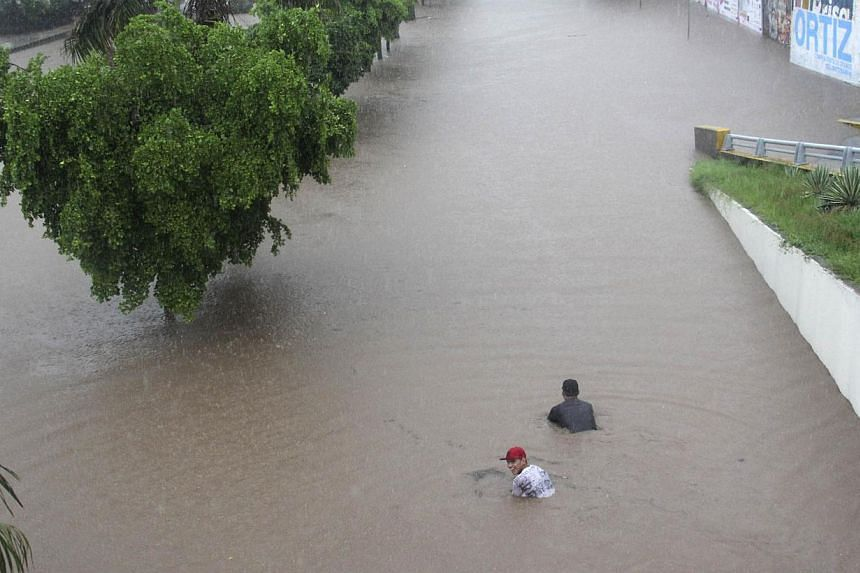 People swim in floodwaters in Culiacan on Sept 19, 2013. At least 101 people have been killed in landslides and flooding caused by especially heavy rain in Mexico over the past week, Interior Minister Miguel Angel Osorio Chong said late on Friday. --
