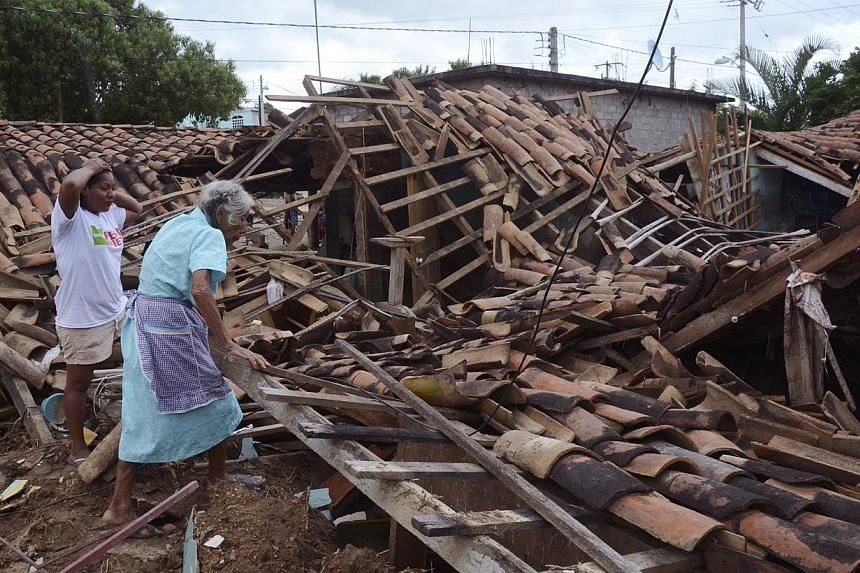 Two women try to salvage what was left of their home after it was destroyed by the rains and floods caused by Tropical Storm Manuel in the village of Salsipuedes, Mexico, on Sept 20, 2013. At least 101 people have been killed in landslides and floodi