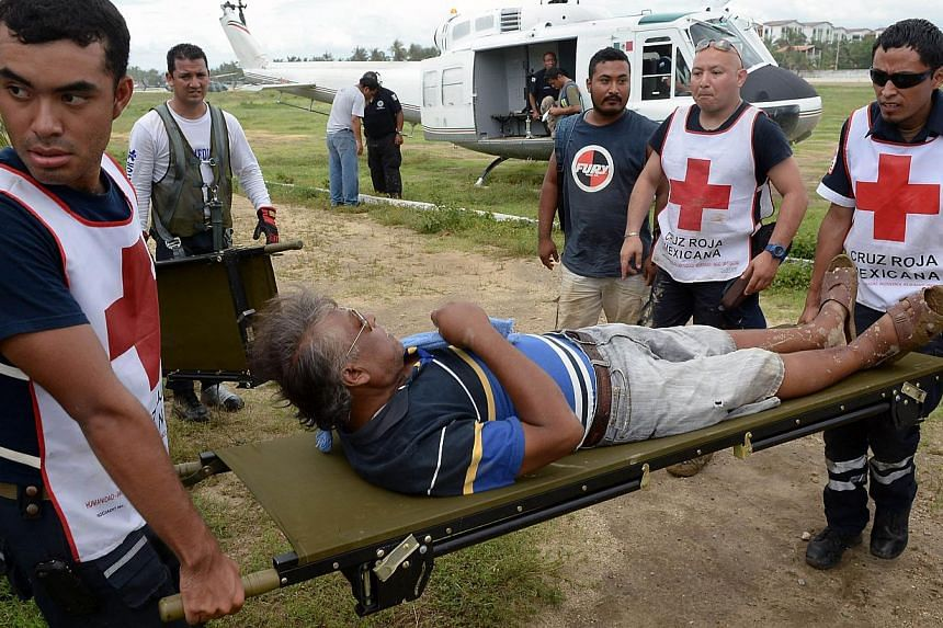 A resident of Coyuca de Benitez, Guerrero state, Mexico is evacuated on Sept 20, 2013. At least 101 people have been killed in landslides and flooding caused by especially heavy rain in Mexico over the past week, Interior Minister Miguel Angel Osorio