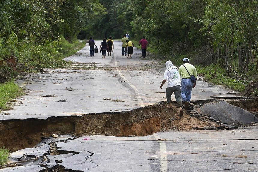 Residents walk along a road leaving La Pintada, state of Guerrero, Mexico, on Sept 19, 2013 as heavy rains hit the country. At least 101 people have been killed in landslides and flooding caused by especially heavy rain in Mexico over the past week,