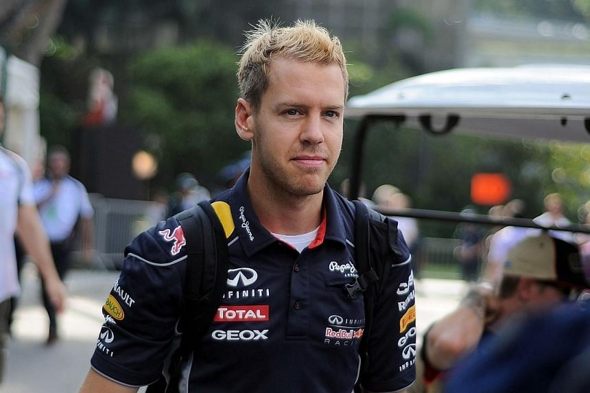Red Bull driver Sebastian Vettel of Germany arrives at the paddock for the third practice session of the Formula One Singapore Grand Prix on Saturday, Sept 21, 2013. Vettel topped the timesheet at the third and final practice session for the 201
