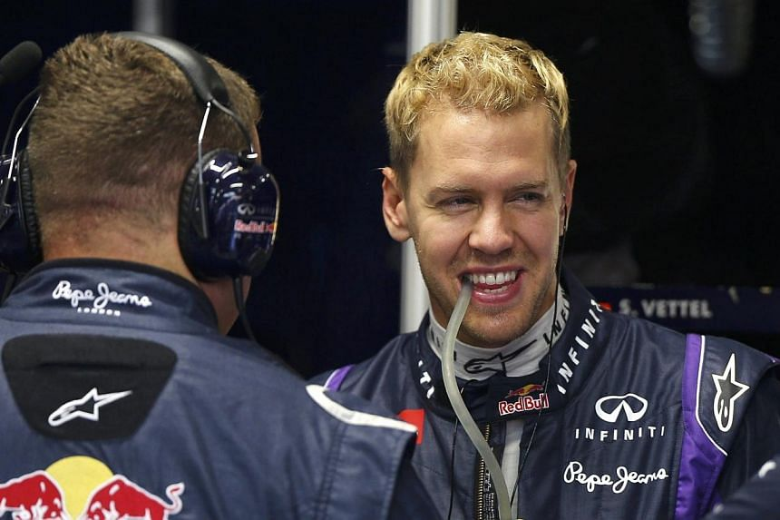 Red Bull Formula One driver Sebastian Vettel of Germany looks on in the team's garage during the Singapore F1 Grand Prix at the Marina Bay street circuit in Singapore on Saturday, Sept 21, 2013. Vettel stormed to his fifth pole position of the season