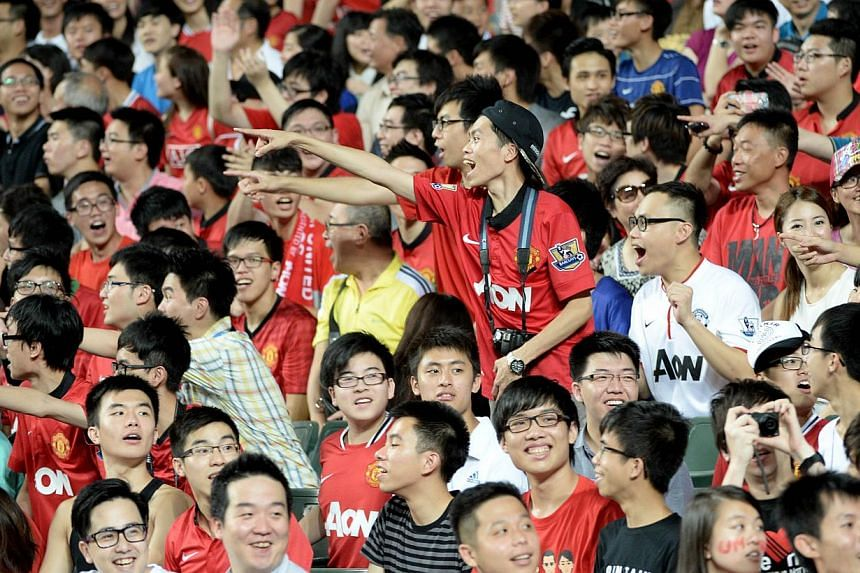 Fans of English Premier League football team Manchester United cheer during a friendly match with Hong Kong team Kitchee at Hong Kong stadium on July 29, 2013. The English Premier League will earn 941 million pounds (S$1.8 billion) from broadcas