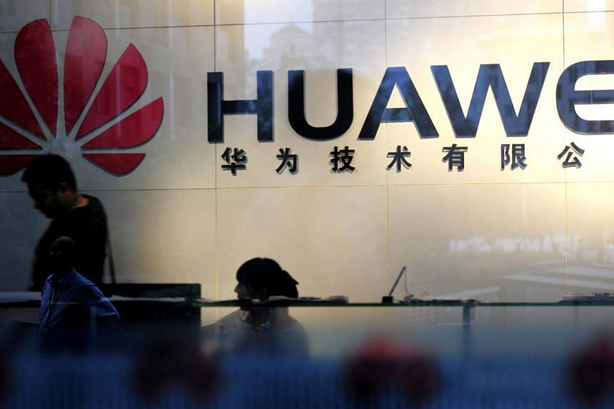 This file photo dated October 8, 2012 shows staff and visitors walking past the lobby at the office of telecommunications equipment firm Huawei Technologies in Wuhan, central China's Hubei province. -- FILE PHOTO: AFP